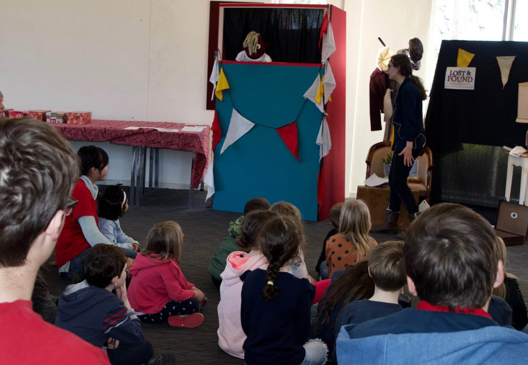An image of children watching a puppet show